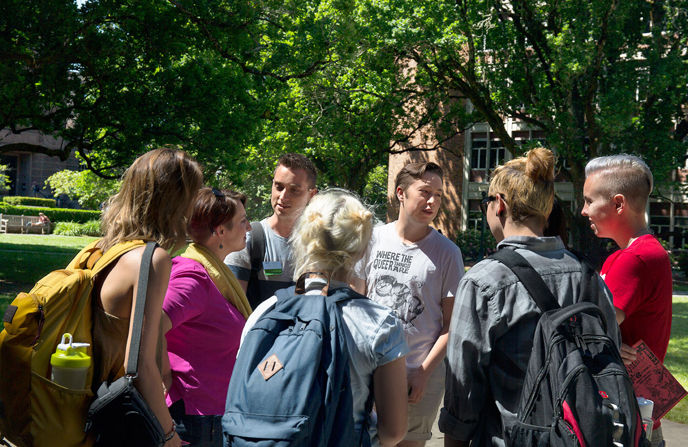 LGBTQ students in stand together in a discussion in the memorial quad.