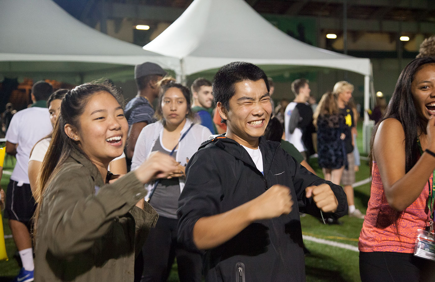Excited crowds of students having a good time on the turf fields at night.