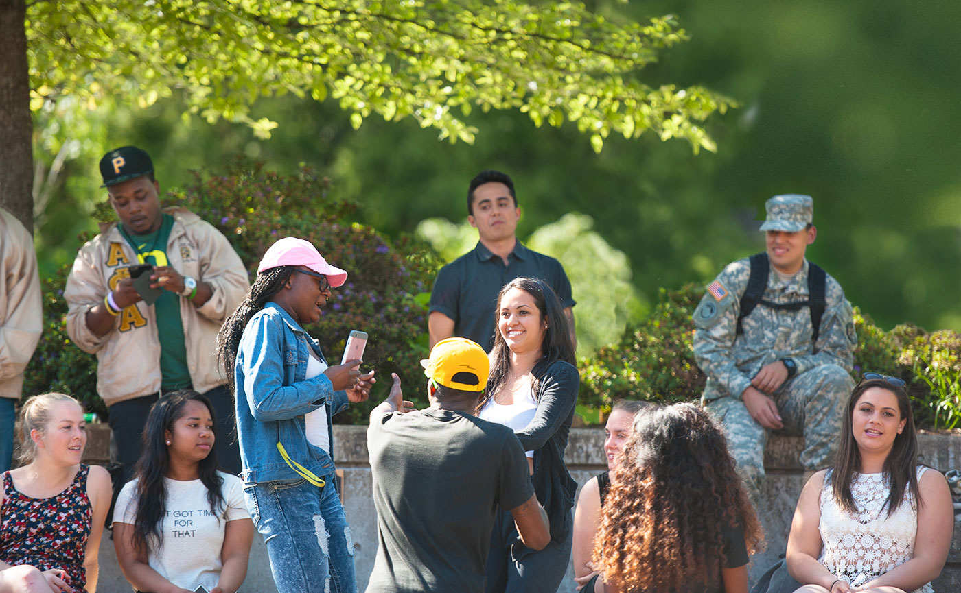 A diverse group of students hang out together in the Erb Memorial Union amphitheater.