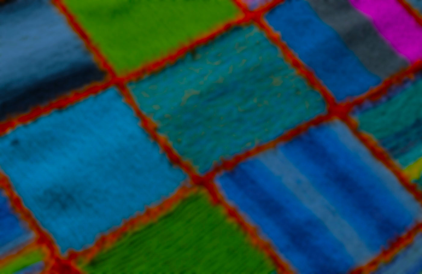 Close up of a blanket with multi-colored squares.