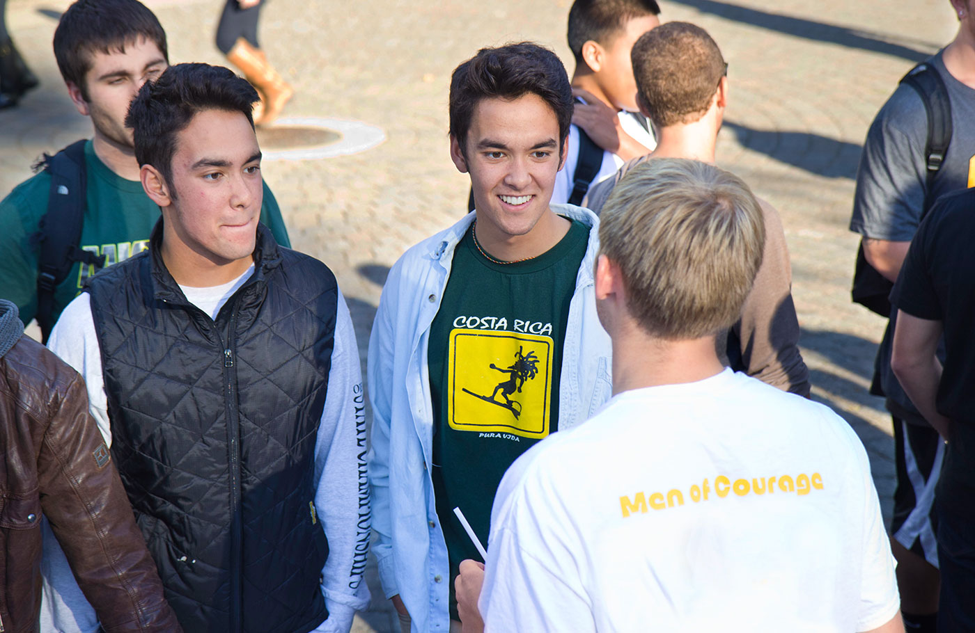 A group of male students talk together in the EMU amphitheater.