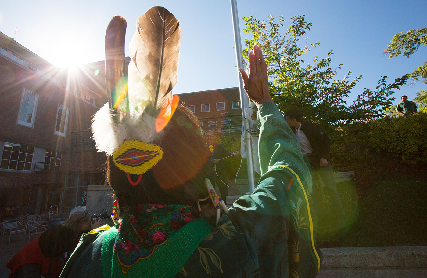 The sun peaks over the top of the EMU as an Native American raises their hand to honor the raising of their tribes flag in the EMU amphitheater.