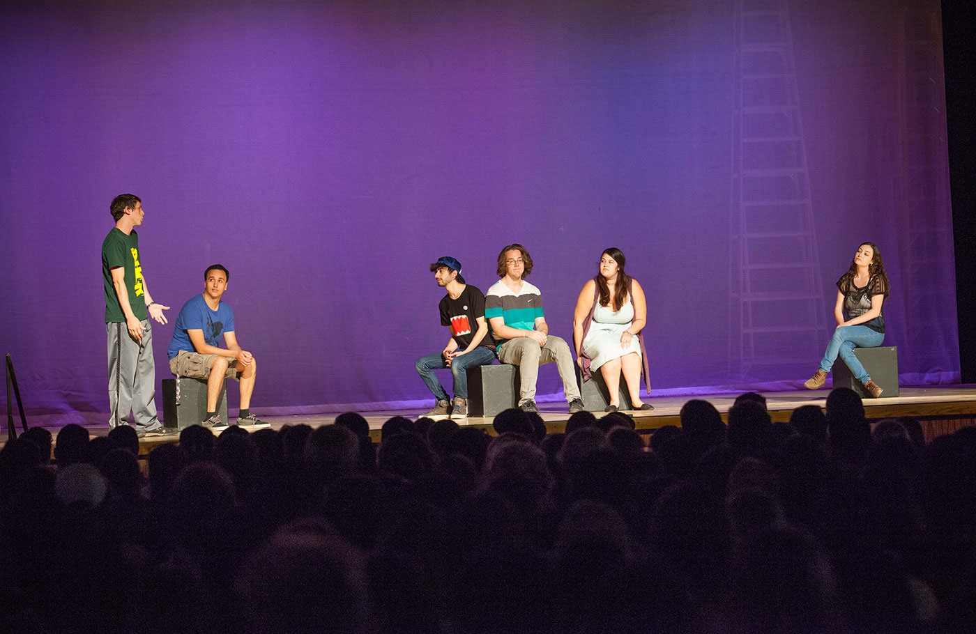 Six students perform on a stage with a purple back drop about sexual wellness issues to a full audience.
