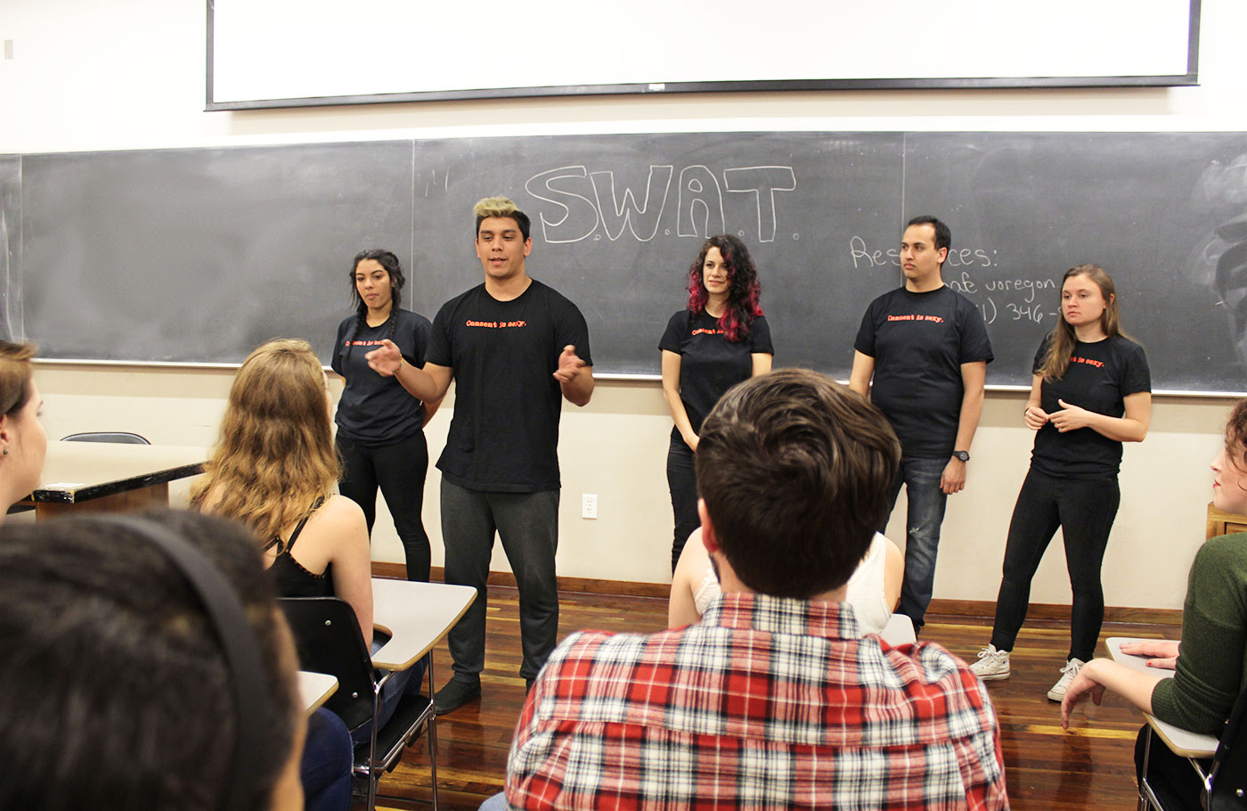 Five student from the Sexual Wellness Advocacy stand in front of a classroom teaching them about sexual wellness.