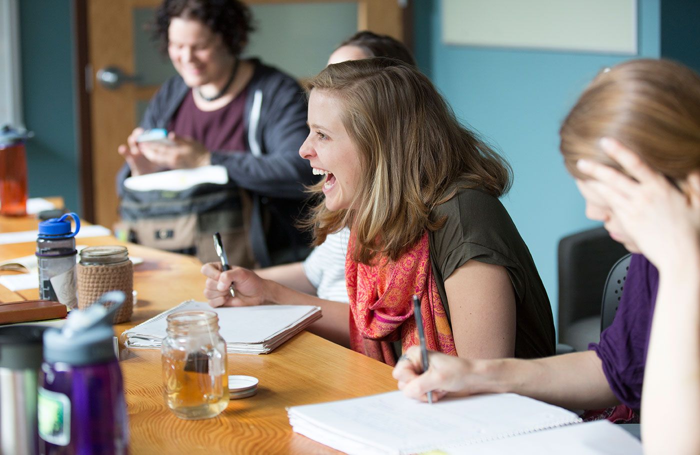 Female students laughing together as they study around a conference table.