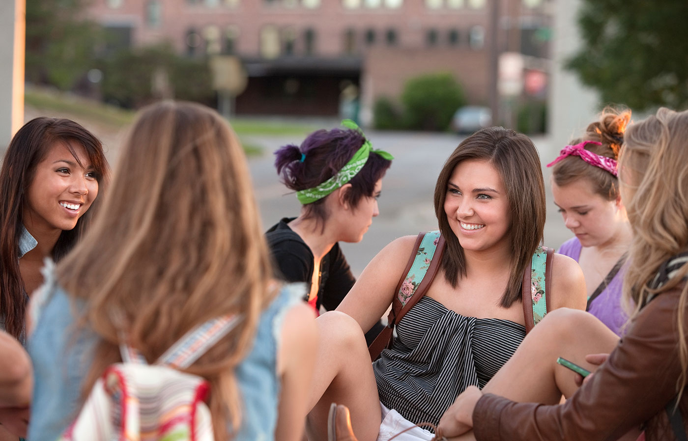 A group of female students hanging out and laughing on campus.